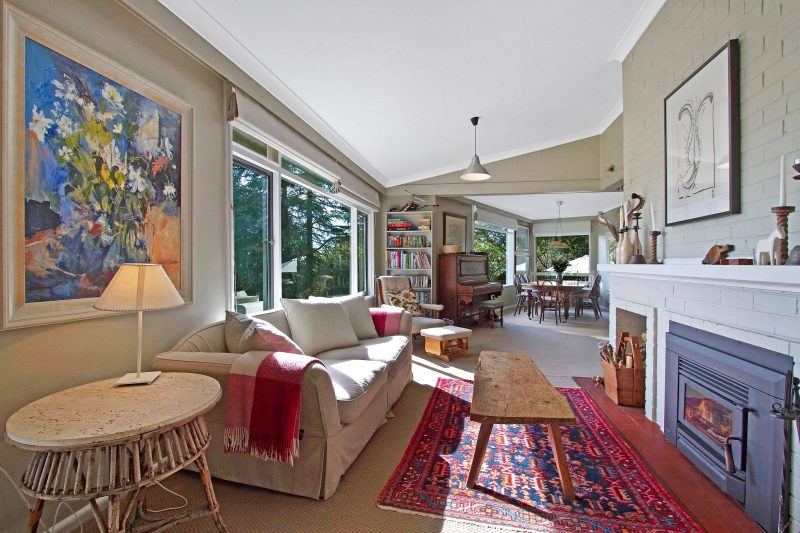 Lounge room with open fire and sunny garden views