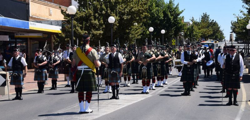Group of Soldiers dressed in Kilts carrying Pipes and Drums and marching down the street.