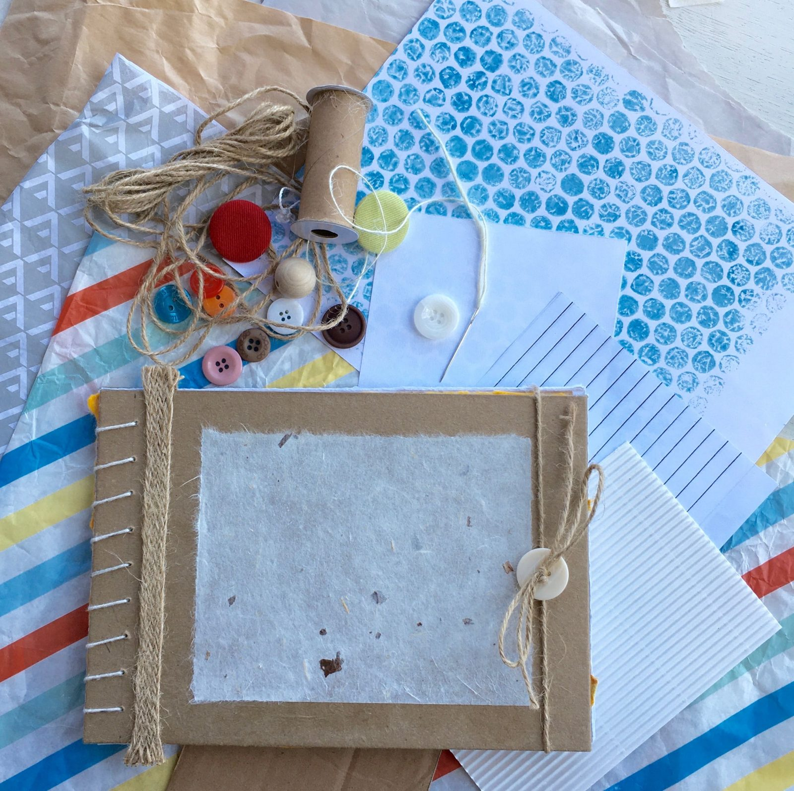 Handmade book, selection of papers, string and buttons
