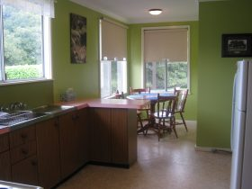 Kitchen with sunny eatery, fridge,electric stove and microwave