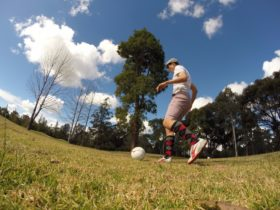 Man wearing golf clothing kicking soccerball