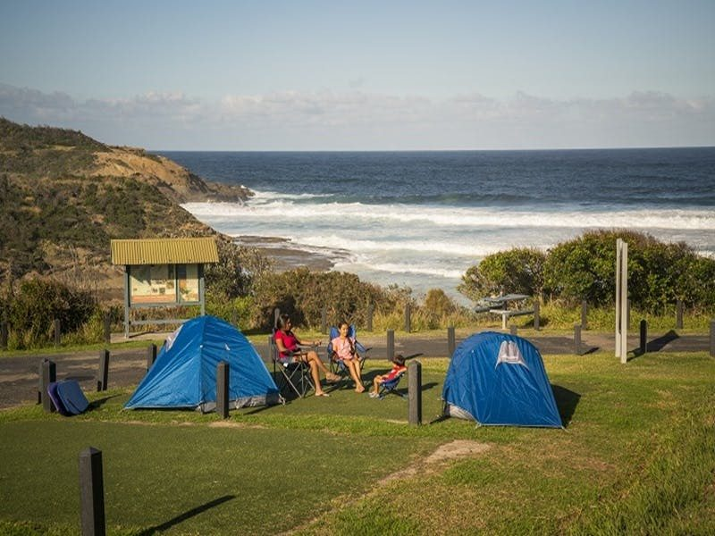 Family sitting beside their tents at Frazer campground, Munmorah State Conservation Area. Photo: Joh