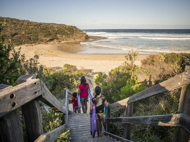 A family walking downstairs to Frazer beach, Munmorah State Conservation Area. Photo: John Spencer/O