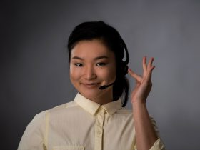 A woman with a headset looking at the camera with a slight smile.