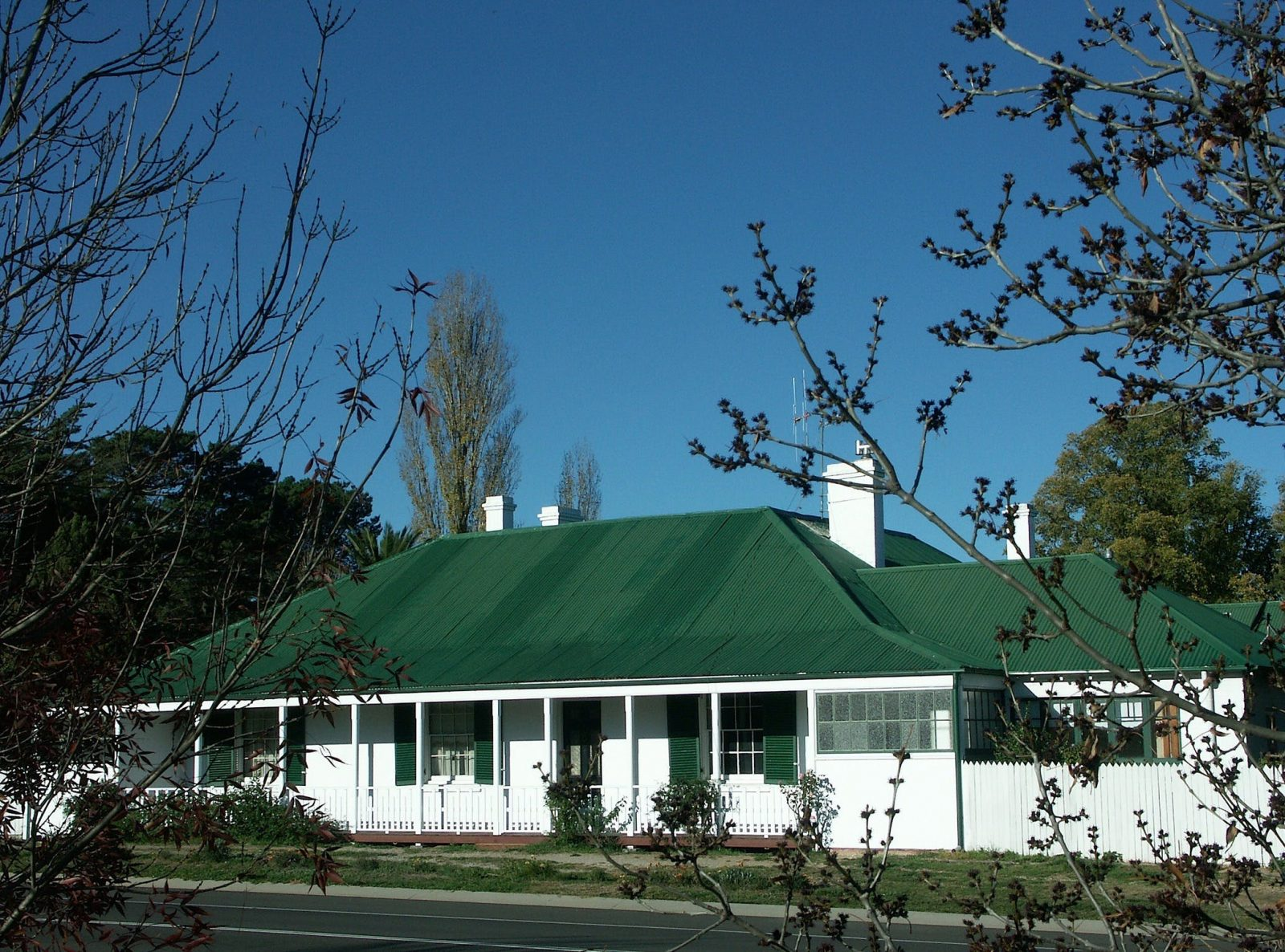 The front of the property. White house with green roof