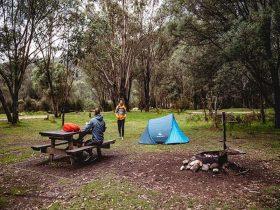 A man sits at a picnic table next to a tent at Geehi Flats campground, Kosciuszko National Park. Pho