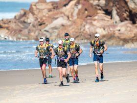 Team running along beach