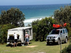Campers with their camper trailer at Gillards campground, Mimosa Rocks National Park. Photo: John Yu