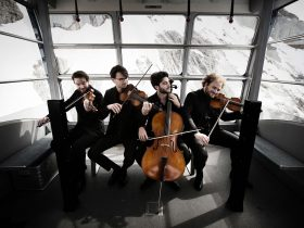 A photo of the Goldmund String Quartet members with their instruments taken with a snowy landscape