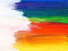 Different colour paints spread across page