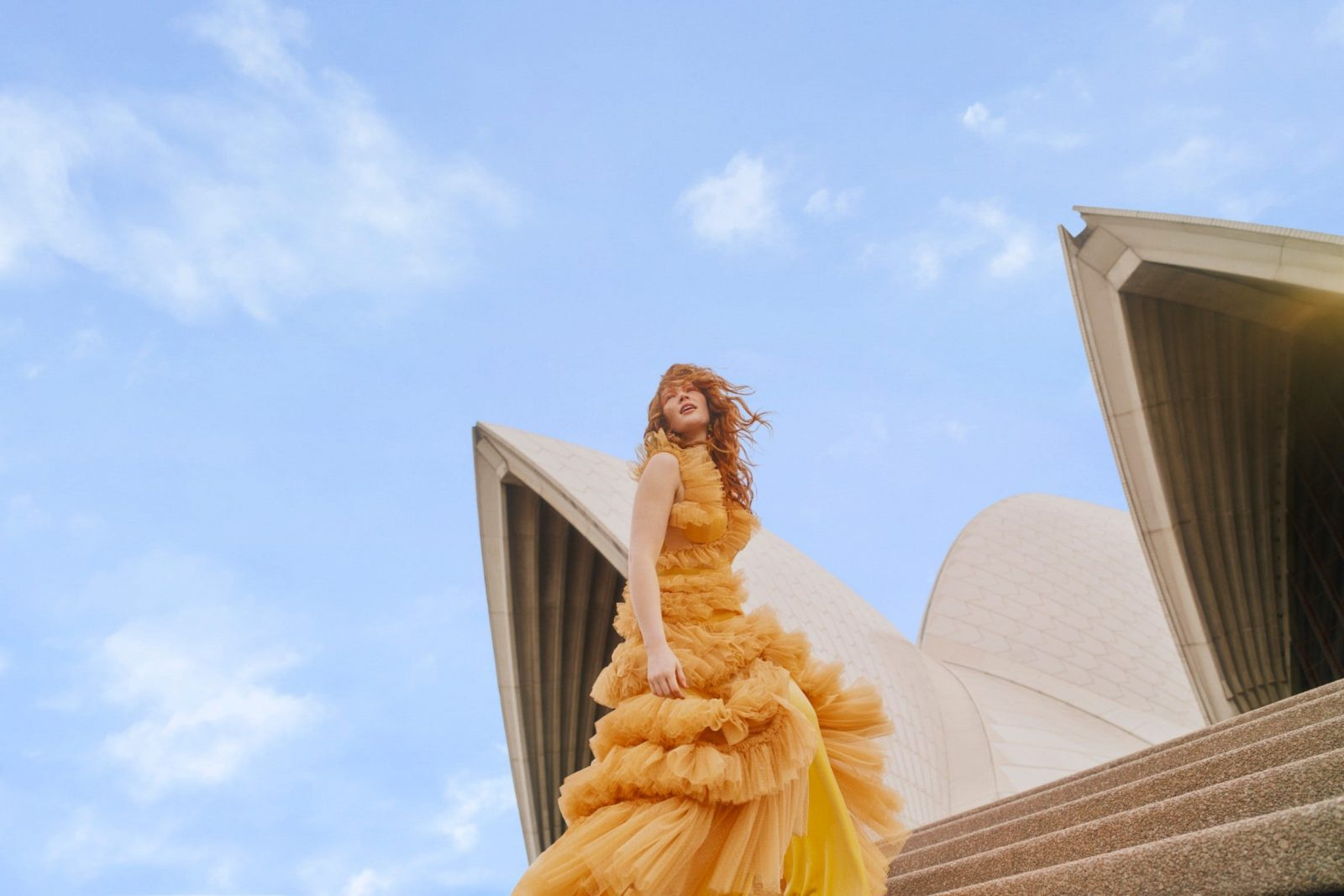 A lady in yellow dress outside the Opera House sails