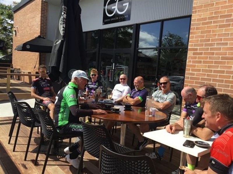 Cyclists enjoying a coffee on the back deck off the cycling shop