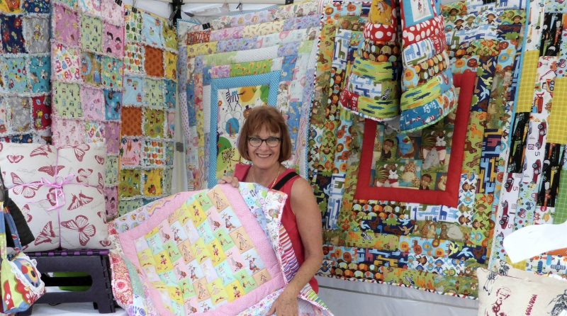 Handmade in the Hunter Markets stallholder showing her handmade quilts.