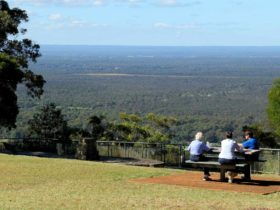 Three visitors sitting at the Hawkesbury lookout. Photo: John Yurasek