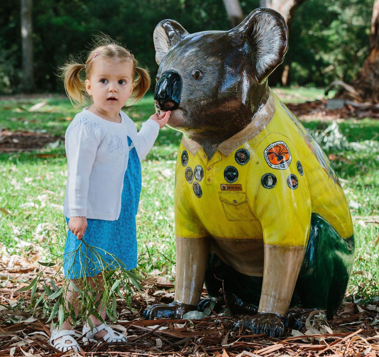 Little girl feeding eucalypt leaves to Hello Koalas sculpture Ranger Riley in the Eucalypt Garden