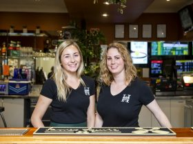 Two female staff members standing behind the bar