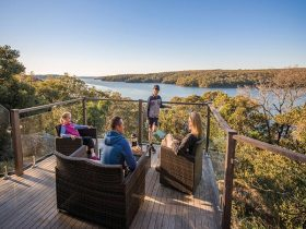 A family enjoying the view from the balcony of Hilltop Cottage in Royal National Park. Photo: John S