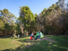 Two campers sitting outside their tent at Hobart Beach campground, Bournda National Park. Photo: Dan