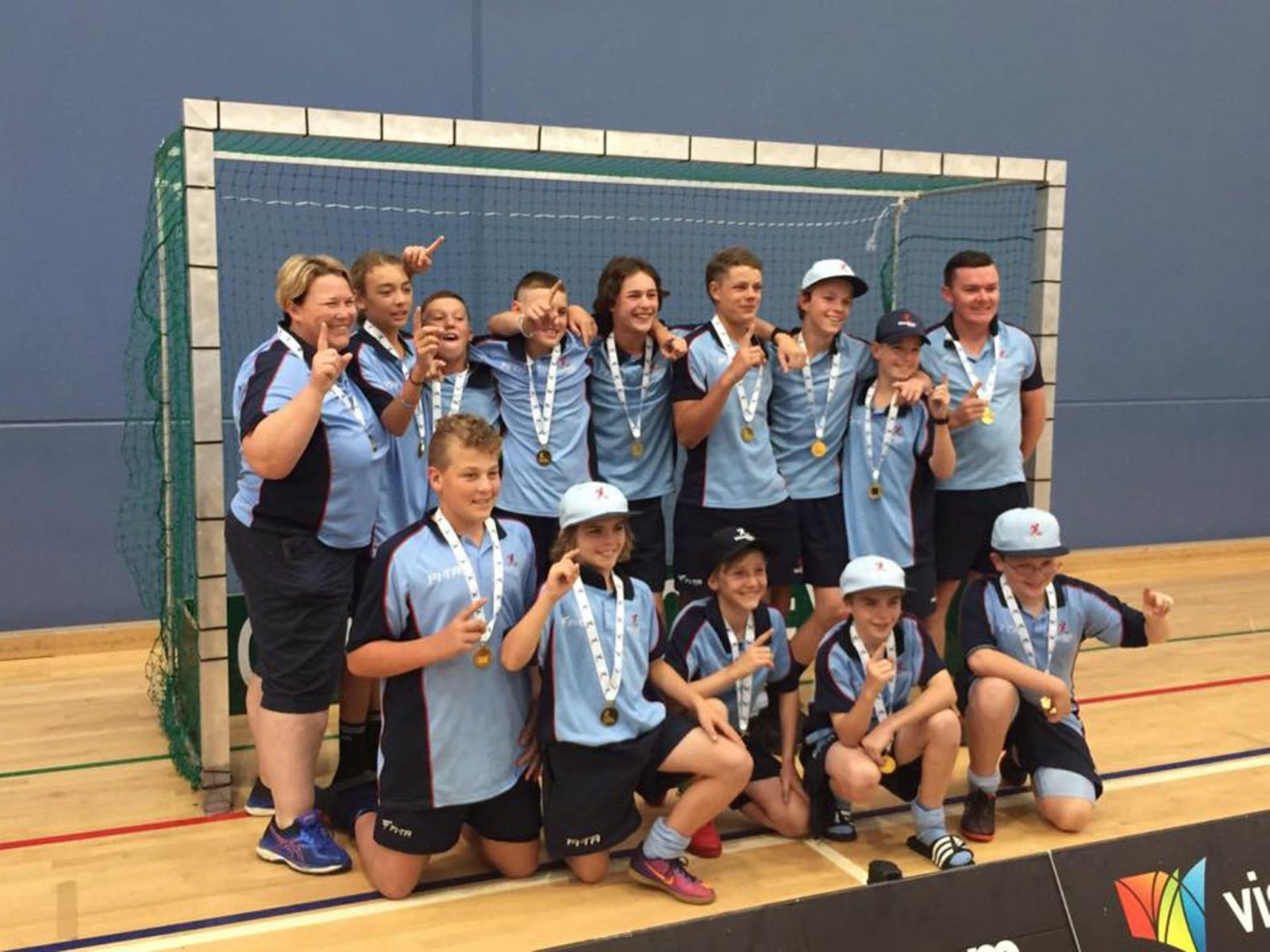 Under 18 boys posing for a photo in the goal net