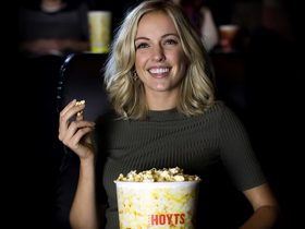 Woman eating popcorn in move theatre