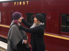 Two 1920s costumed ladies in front of a vintage train