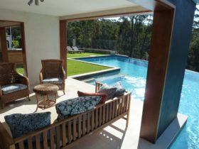 Private infinity pool overlooks bush lake and ocean