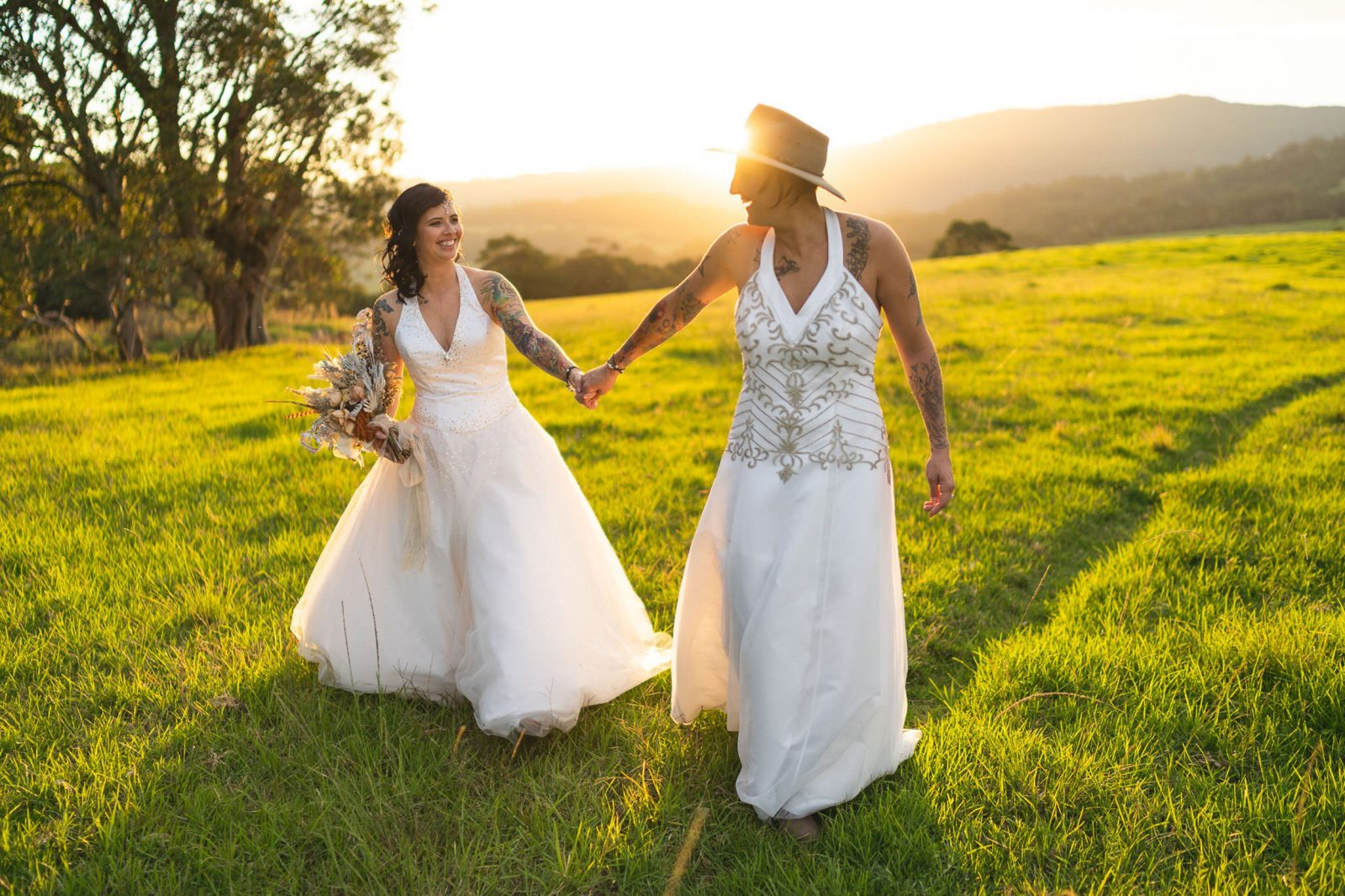 Two brides walk through a field at golden hour