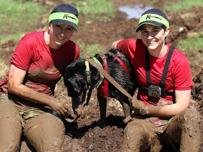 Two women with dog smiling in mud