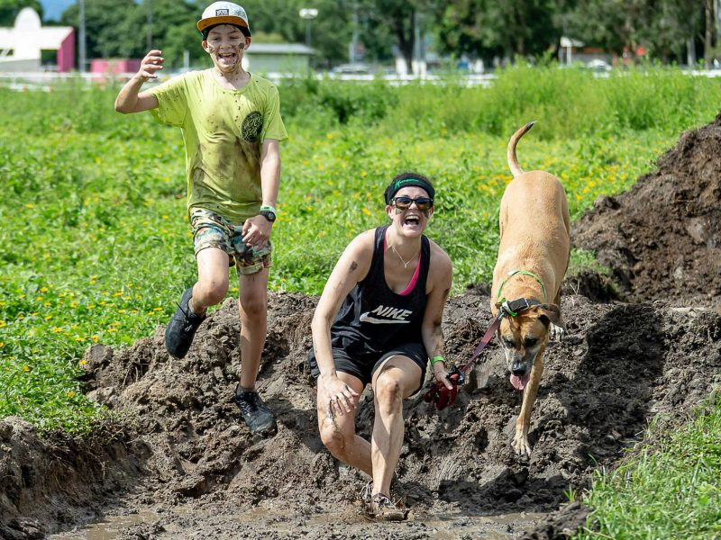 Boy woman and dog laughing entering mud