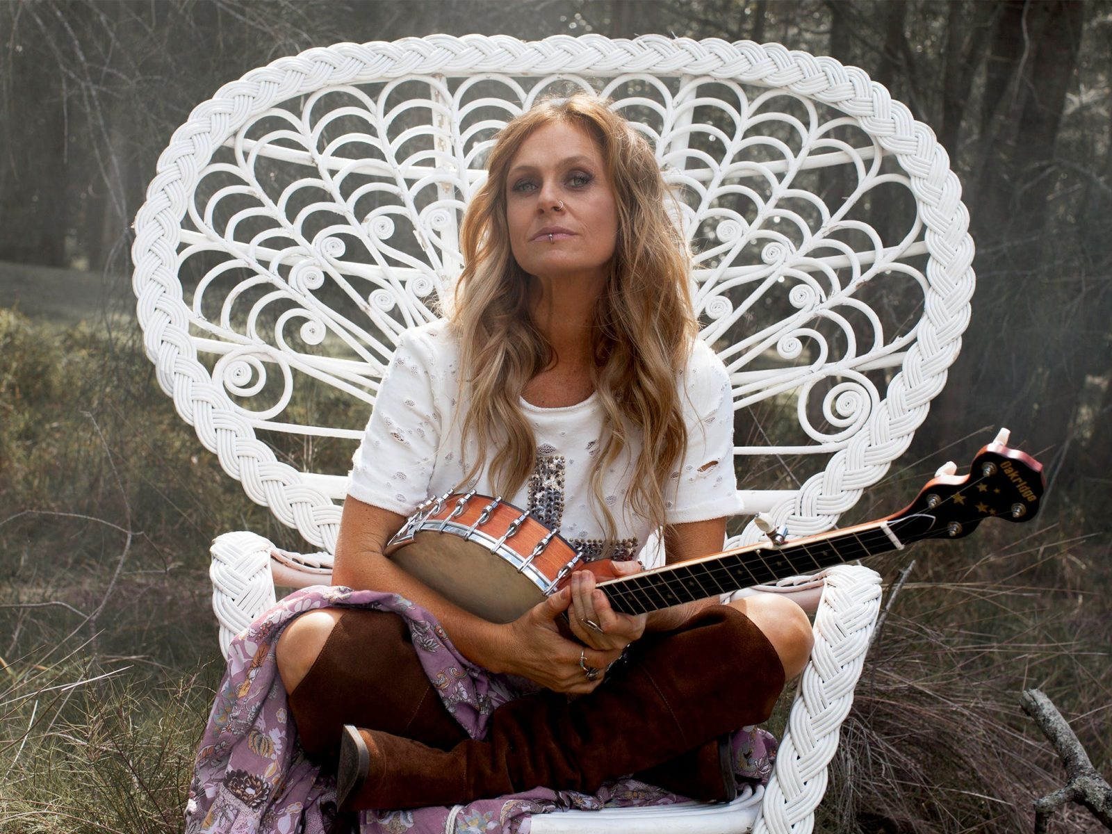 Kasey Chambers in a white chair with a banjo