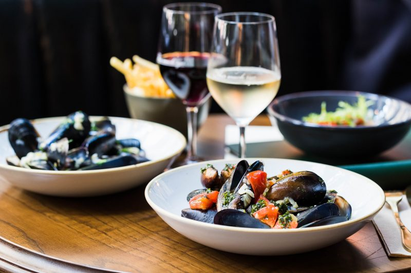 Enjoy some mussels and fries with a glass of wine