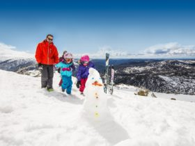 Family atop the mountain with their skis and a snowman