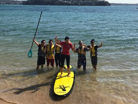 People gathered around a paddle board at the beach in Bundeena