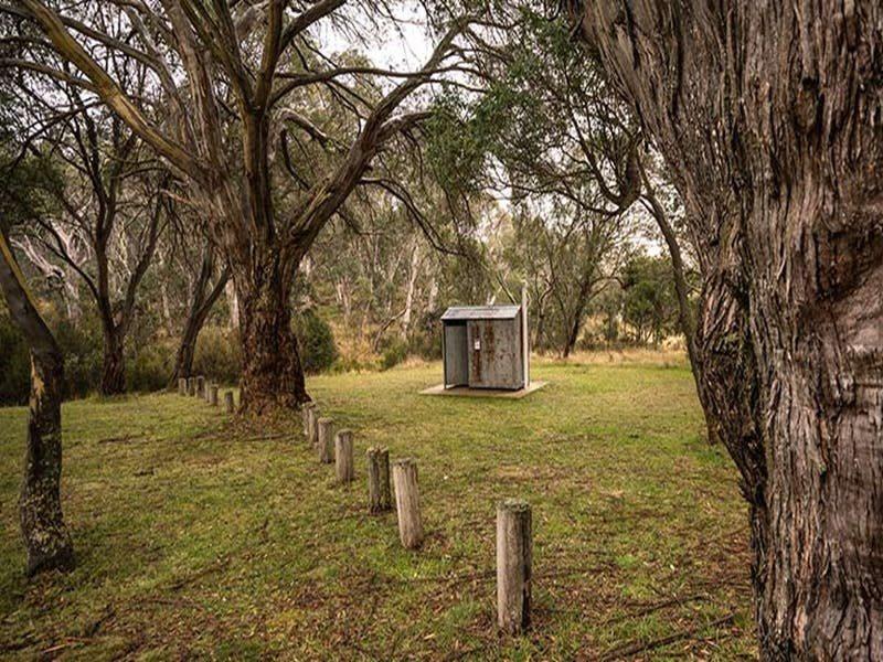 Non-flush toilet tin building among trees, Long Plain Hut campground, Kosciuszko National Park. Phot