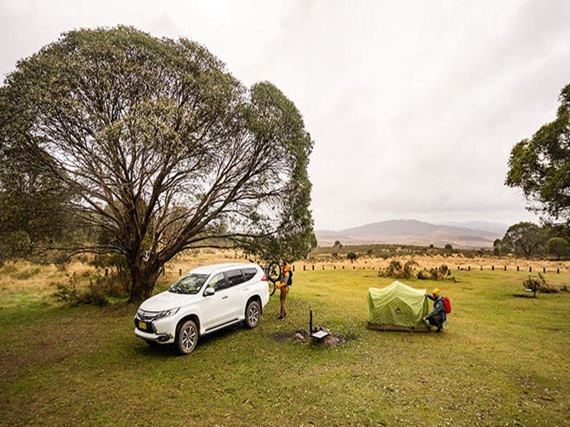 A man sets up a tent next to a fire ring and car at Long Plain Hut campground, Kosciuszko National P