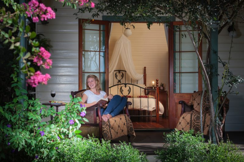 Photo of woman reading on verandah at Maddies of Bolwarra Bed and Breakfast
