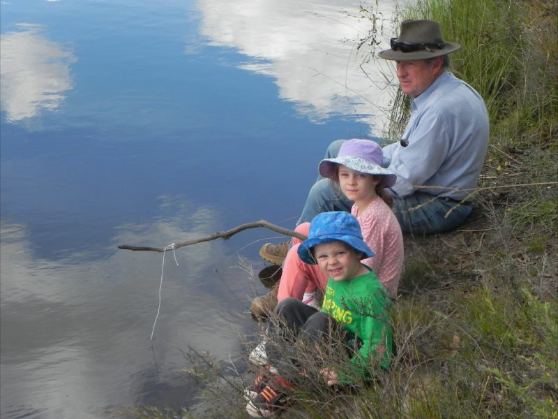 Man and two children fishing by stream