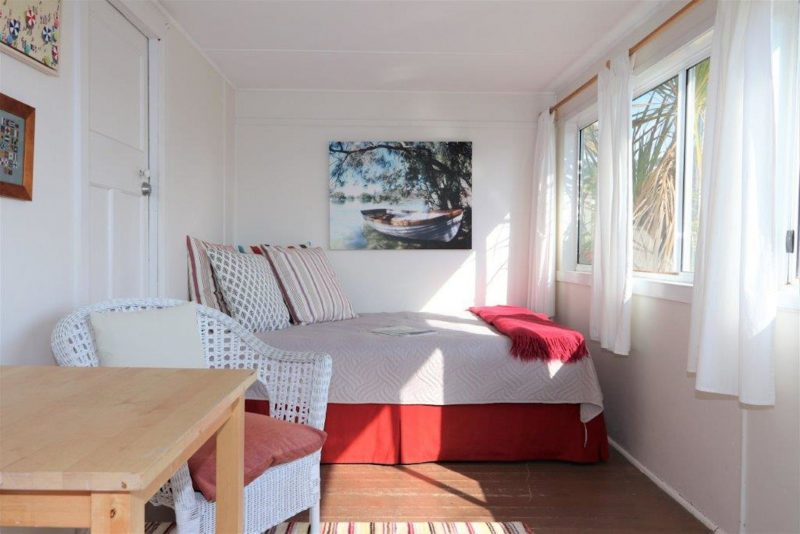 Sunroom with view to the beach contains breakfast table and queen sized day bed.