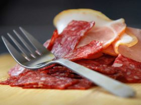 Sliced salami on wooden board with silver fork on top