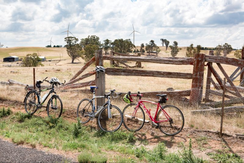 Three bicycles lean up against a wire fence beside an old timber cattle yard.