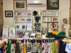 Display of handmade jewellery, towels, cards, kniteed jumpers and history books