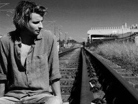 Singer Mitch King sitting on rail tracks