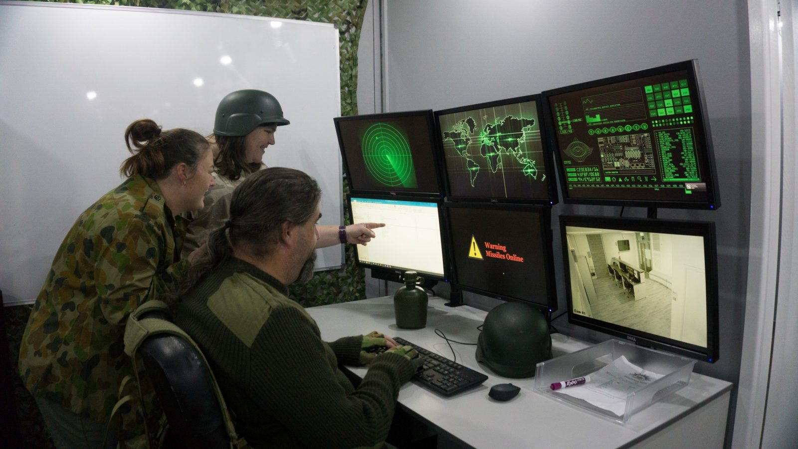 3 people dressed in army gear looking at 6 monitors