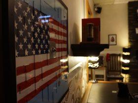 A view of an American flag, a desk, bookshelf and lights