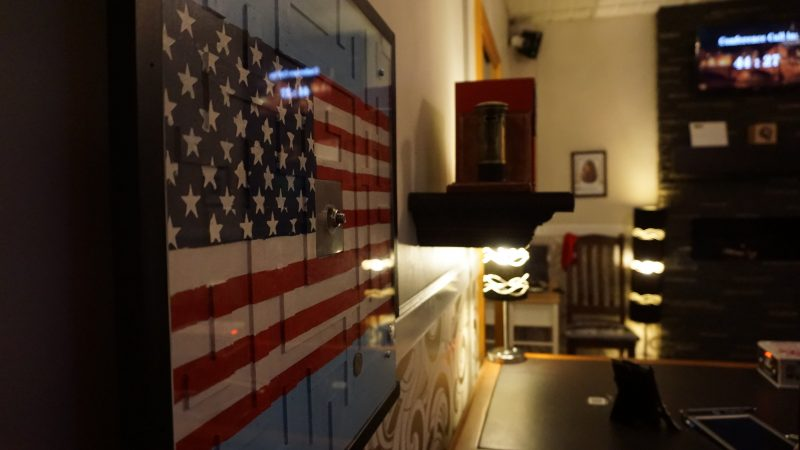 A view of an American flag, a desk, bookshelf and lights