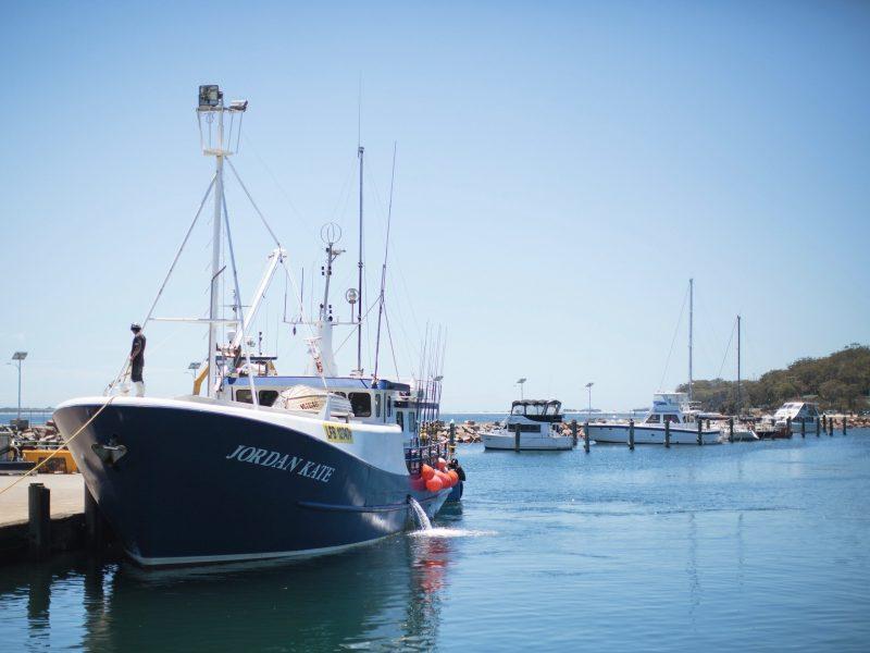 Blue fishing boat at Nelson Bay's marina tied to the wharf