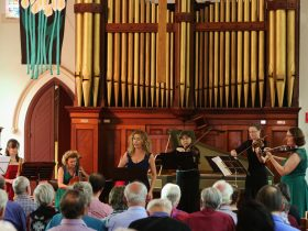Singer and chamber ensemble perfoming in front of organ