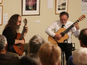 Two guitarists playing in art gallery