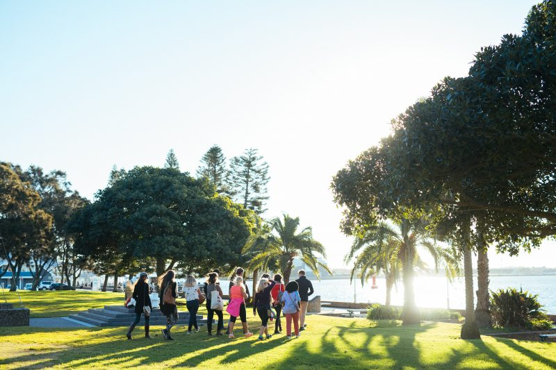 A small group walks on Newcastle foreshore on a guided Newcastle Afoot walking tour