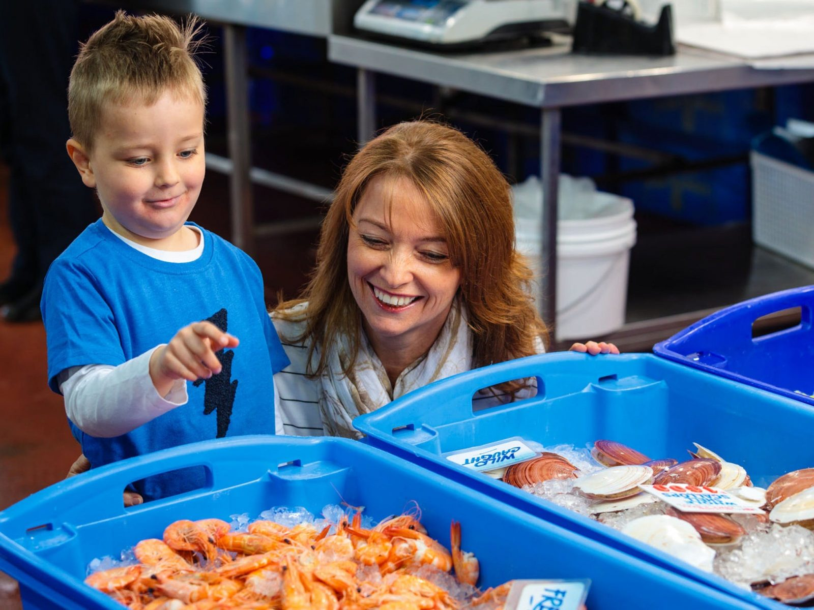 Mother and son looking at fresh seafood in buckets
